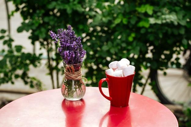 Bevanda calda con marshmallow tostato in tazza rossa sul tavolo rosso decorato con lavanda in vaso