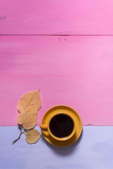 Caldo nero caffè aromatico americano su un vecchio tavolo in legno rosa blu con foglie di autunno