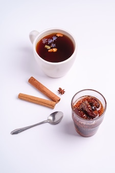 Tè aromatico nero caldo vicino alla marmellata di fichi, atmosfera natalizia per la colazione con anice e cannella su superficie bianca, vista angolare