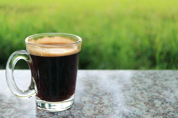 Caffè nero caldo in un bicchiere trasparente con prato verde sfocato