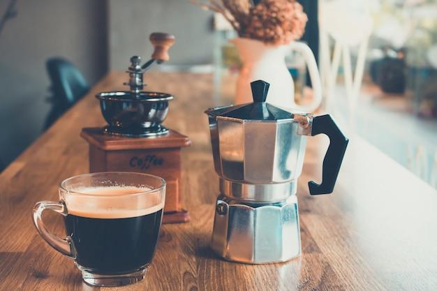 Caffè nero caldo con caffettiera d'epoca sul tavolo nella caffetteria