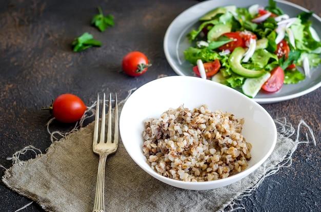 Porridge di grano saraceno caldo con burro fuso nella ciotola nera e insalata di verdure