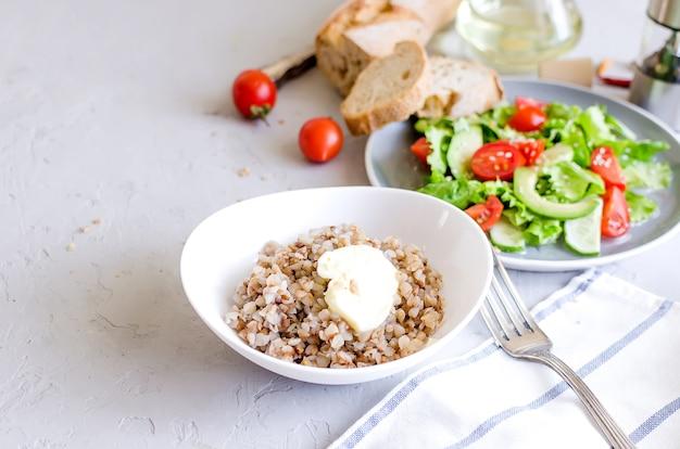 Porridge di grano saraceno caldo con burro fondente nel piatto bianco e insalata di verdure
