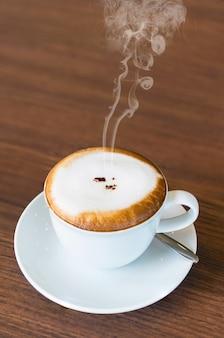 Tazza di caffè caldo cappuccino sul tavolo di legno