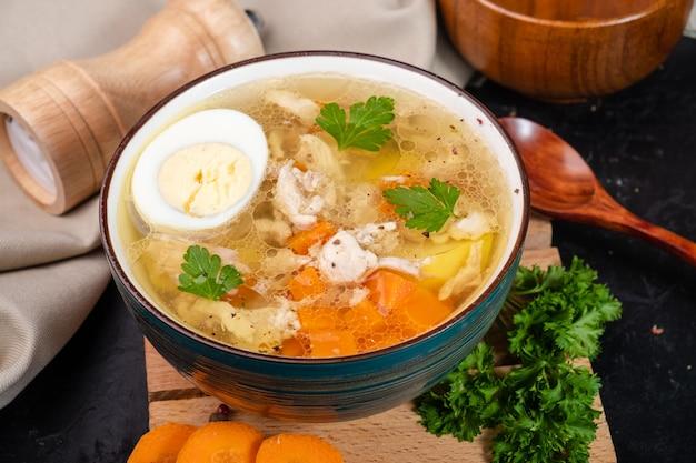 Zuppa di pollo calda con verdure a base di carne e un uovo su sfondo nero.