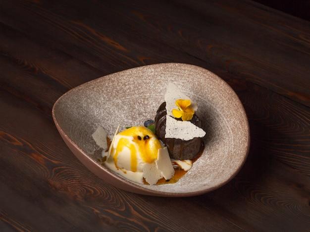 Brownie al cioccolato caldo servito con una pallina di gelato e guarnito con frutti di bosco e fiori