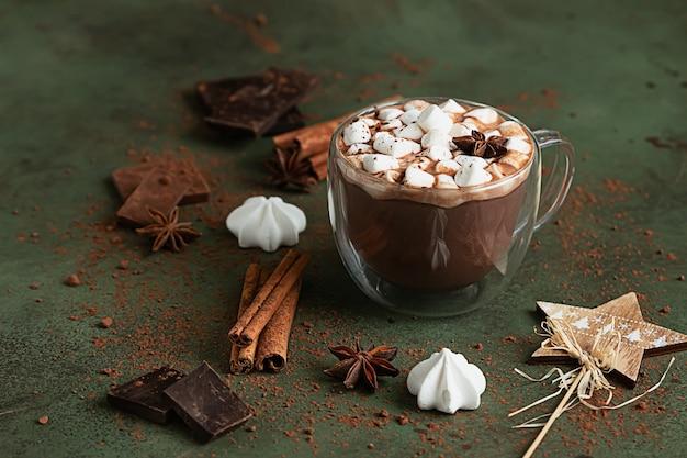Cioccolata calda o cacao con marshmallow e anice, pezzi di cioccolato, meringa e spezie.