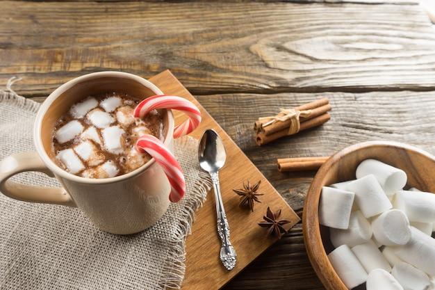 Cioccolata calda, marshmallow e cannella sul tavolo rustico