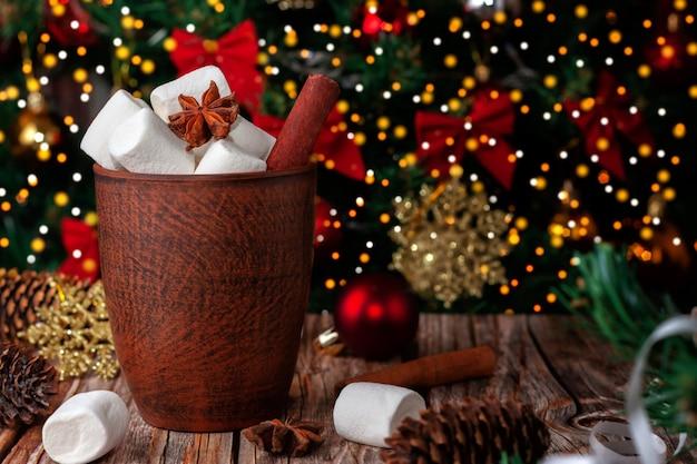 Tazza di cioccolata calda e marshmallow sullo sfondo dell'albero di natale
