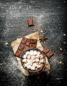 Cioccolata calda con cioccolato amaro e cannella sulla lavagna nera.