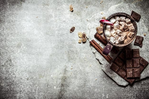 Cioccolata calda con cannella, zucchero di canna e cioccolato fondente su cemento.