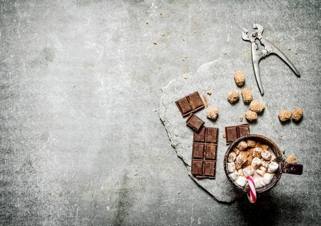 Cioccolata calda con cannella, zucchero di canna e cioccolato fondente. su un tavolo di pietra.