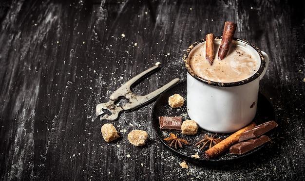 Cioccolata calda con cannella e taglierine per lo zucchero. su sfondo nero rustico.