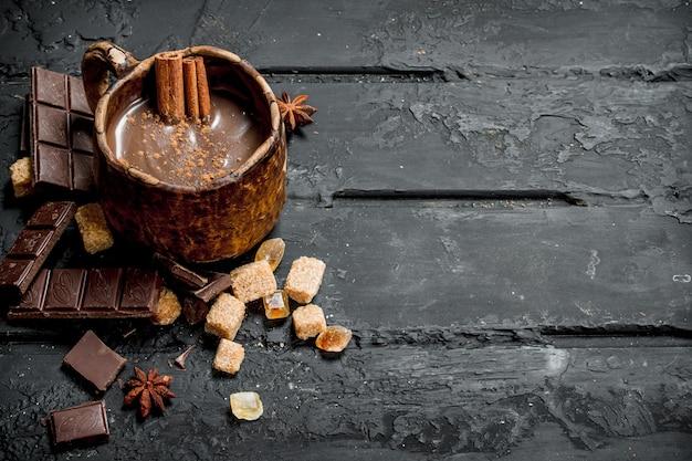Cioccolata calda con bastoncini di cannella sul tavolo rustico nero.
