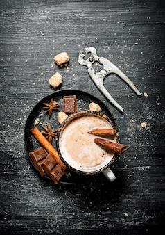 Cioccolata calda con frese cinnamonnd per lo zucchero sul tavolo rustico nero.