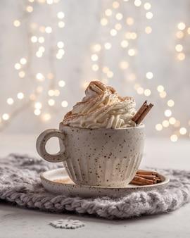 Cioccolata calda con panna e stecca di cannella in una tazza di ceramica. Foto Premium