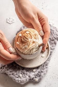 Cioccolata calda con panna e stecca di cannella in una tazza di ceramica.
