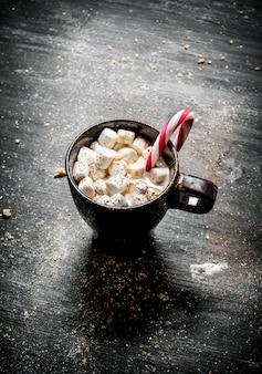 Cioccolata calda con marshmallow e caramello sulla lavagna nera.