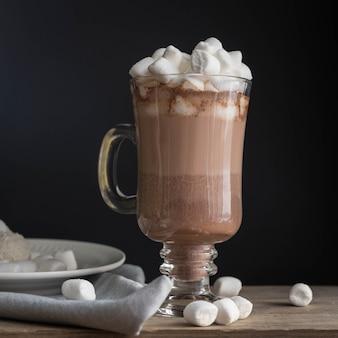 Cioccolata calda con marshmallow in una tazza di vetro su un tavolo di legno bevanda calda e un ramo di abete rosso