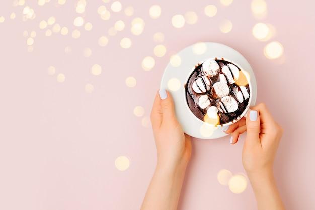 Cioccolata calda con marshmallow in mano di donna su sfondo rosa pallido