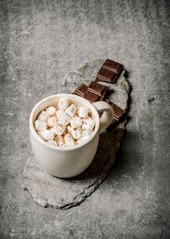 Cioccolata calda con marshmallow e cioccolato amaro sul tavolo di cemento
