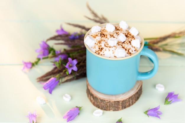 Cioccolata calda con marshmallow in una tazza blu