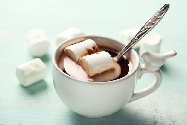 Cioccolata calda con marshmallow in tazza, su fondo in legno colorato