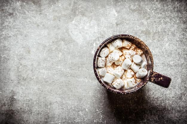 Cioccolata calda con marshmallow. su uno sfondo di pietra.