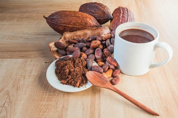 Tazza di cioccolata calda con cacao in polvere e fave di cacao su tavola di legno