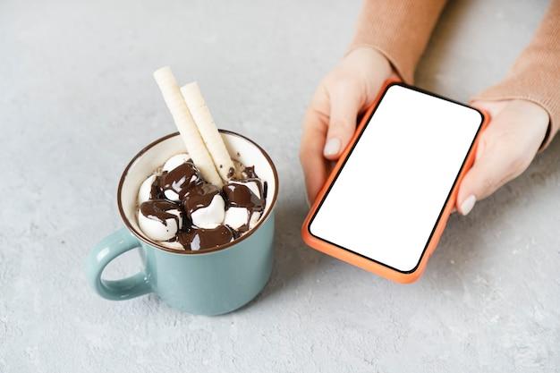 Tazza di cioccolata calda cosparsa di marshmallow e mani di donna che tengono smartphone con schermo bianco vuoto per lo spazio della copia.