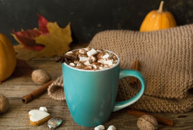 Cioccolata calda con marshmallow in una tazza di ceramica blu con foglie di autunno e zucche su un tavolo di legno. il concetto di hygge, accogliente autunno, ringraziamento, caduta. bevande calde autunno still life.