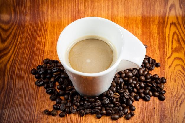 Caffè caldo e chicchi di caffè su uno sfondo di legno.