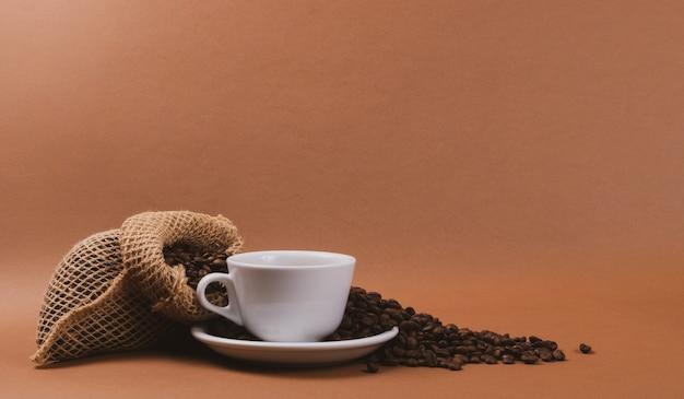 Tazza di caffè e chicchi di caffè caldi nella borsa di tela da imballaggio
