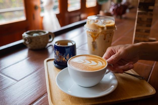 Tazza di caffè caldo a portata di mano con sfondo bokeh, colore vintage, tempo di relax, tempo del mattino