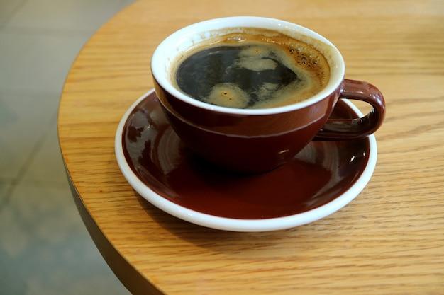 Caffè caldo in tazza marrone scuro isolata sulla tavola di legno rotonda