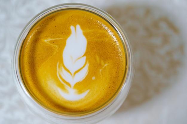 Latte art al caffè caldo con schiuma di latte su un bicchiere