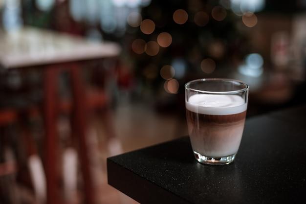Latte caldo del caffè sulla parete dell'esposizione di feste di natale