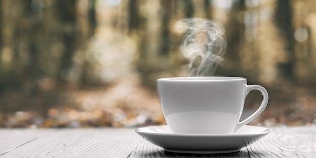 Caffè caldo sul tavolo su uno sfondo autunnale
