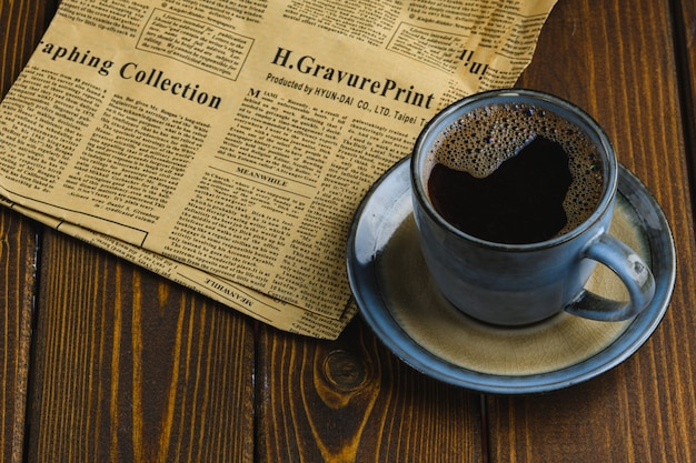 Caffè caldo sul tavolo con un giornale