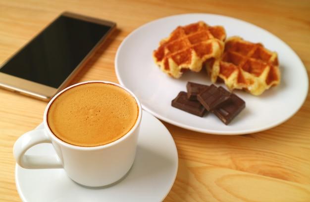 Caffè caldo con dolci sfocati e telefono cellulare a schermo vuoto
