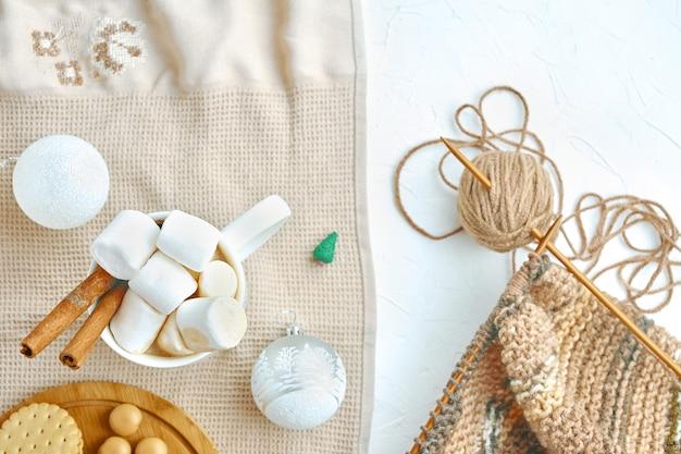 Caffè caldo con biscotti, marshmallow, cannella, decorazioni natalizie e sciarpa per maglieria