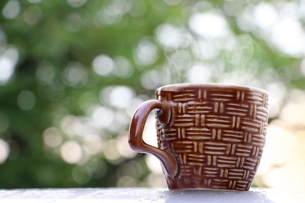 Caffè caldo con la prima colazione del vapore con boken nei precedenti del giardino