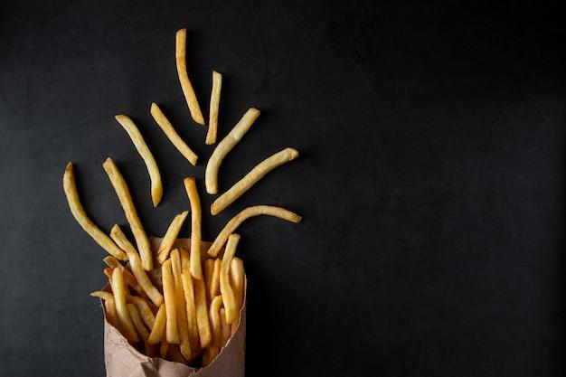Patatine fritte croccanti calde in un sacchetto di carta su uno sfondo nero. gustoso fast food americano.