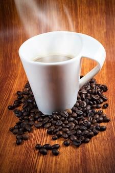 Tazza di caffè calda e fagioli con fumo.