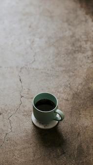 Tazza di caffè calda sullo sfondo del telefono cellulare con pavimento in cemento