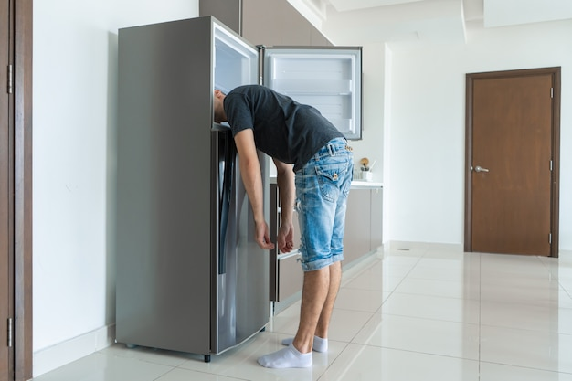 Nelle giornate calde il ragazzo si raffredda con la testa nel frigorifero