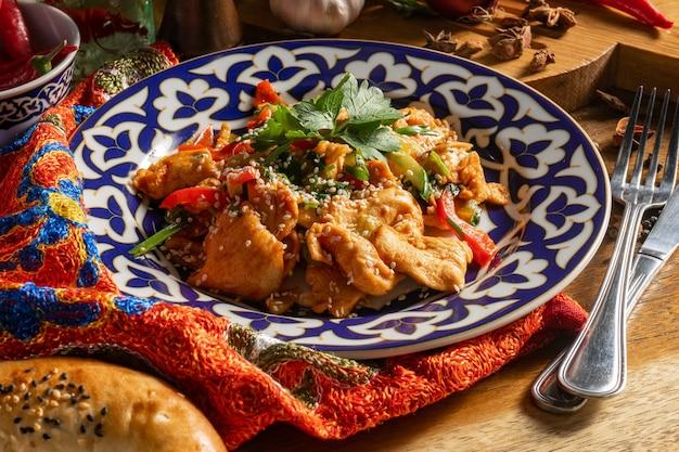 Piatto caldo humo. petti di pollo fritti con peperoni dolci e cetrioli in salsa di soia e semi di sesamo su un piatto tradizionale uzbeko.