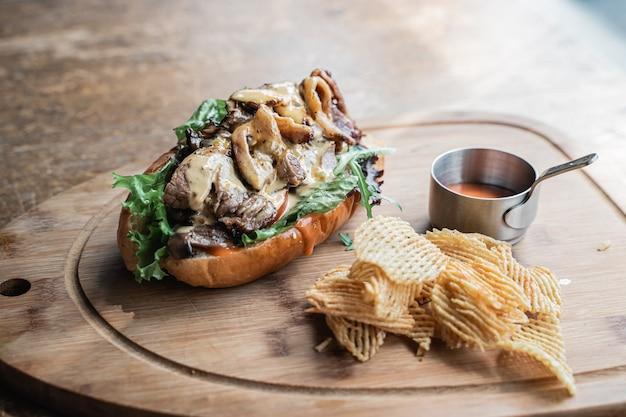 Un piatto di hot dog con griglia di patate fritte servito su un vassoio di legno sul tavolo
