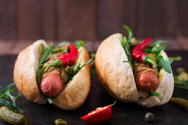 Hot dog con sottaceti, capperi e rucola sul tavolo di legno.