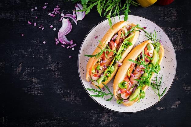 Hot dog con salsiccia, cetriolo, pomodoro e cipolla rossa sul tavolo scuro. vista dall'alto. lay piatto. copia spazio